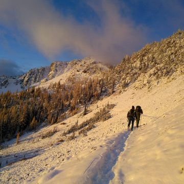 Travis King and friend on a snowy hike up Harts Pass to retrieve cameras on a 24 mile day hike