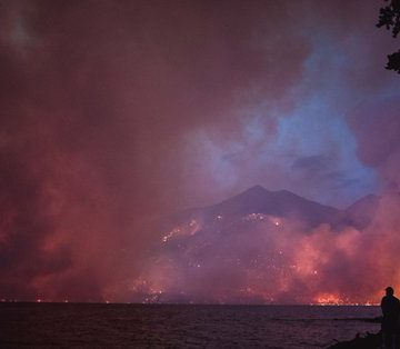 Two people stand and watch the purple and orange blaze of the Howe Ridge fire in Montana's Glacier National Park on August 12, 2018