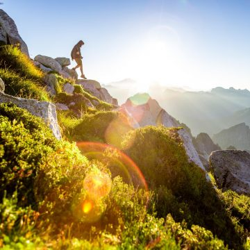 A hiker climbs down a rocky, green hillside with the sun shining in the background