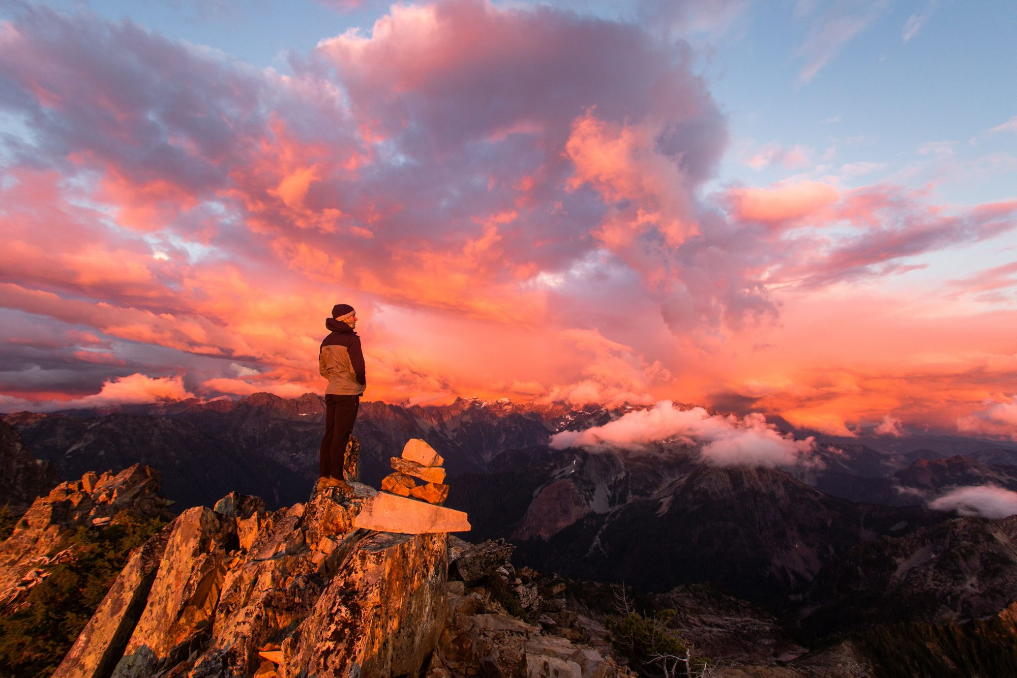 Person stands on top of a ridge overlooking the mountains at sunrise. The clouds and sky are bright pink with hues of yellow and gold.
