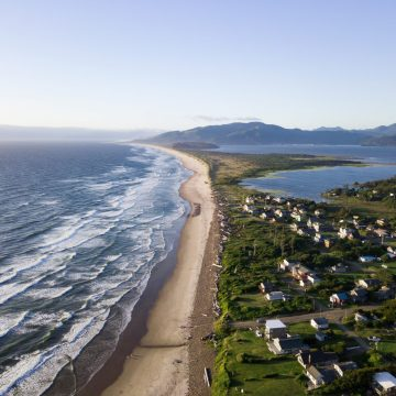 Aerial view of narrow strip of land lined by homes between Pacific Ocean and Tillamook Bay